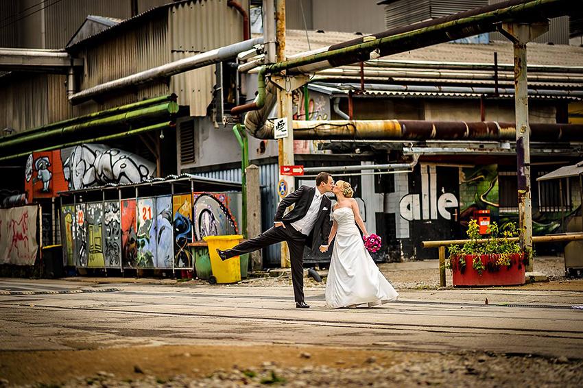 Hochzeitspaar lustiges Foto vor Graffitti Industriekulisse