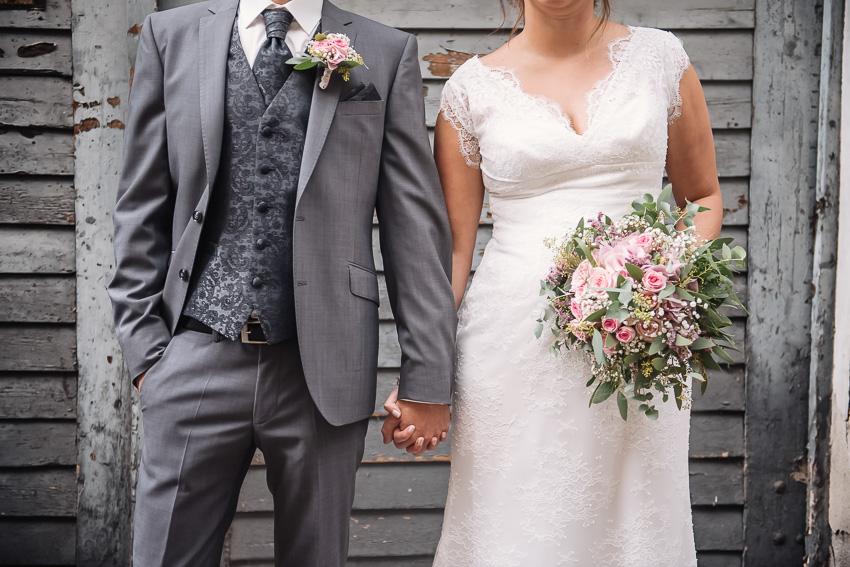 Brautpaarshootig vor alter Holztüre mit Brautstrauss